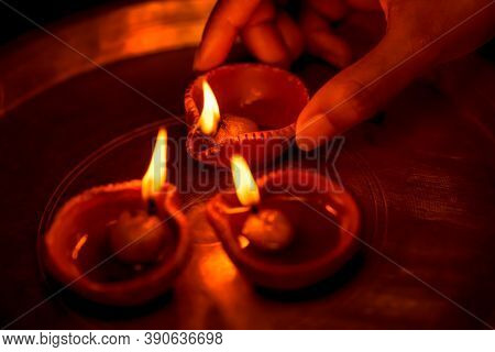 Indian Woman Or Girl Holding A Lit Clay Diya In Her Hand And Illuminating Other Oil Lamps With It In