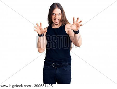 Young adult man with long hair wearing goth style with black clothes smiling funny doing claw gesture as cat, aggressive and sexy expression