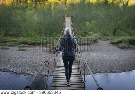 A Lonely Girl Is Walking On A Suspension Bridge. Suspension Bridge Over The River. Solitude With Nat