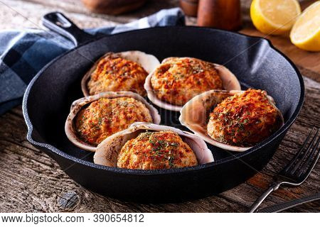 Delicious Oven Baked Stuffed Clams On A Rustic Wood Table Top.