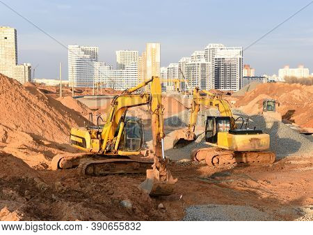 Group Of The Excavators Working On Dig Ground Trenching At Construction Site. Backhoe On Groundwork