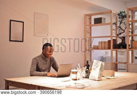 young man in front of a computer in a co-working space