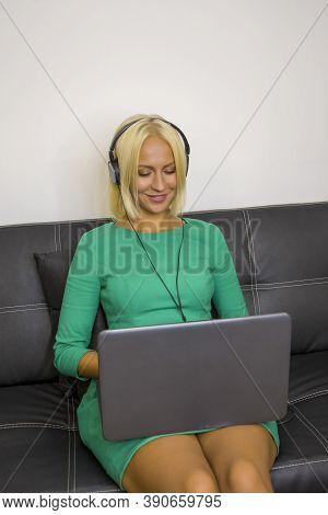 A Young Woman About 30 Years Old Is Sitting On The Sofa With Headphones And A Laptop. Perhaps She Is