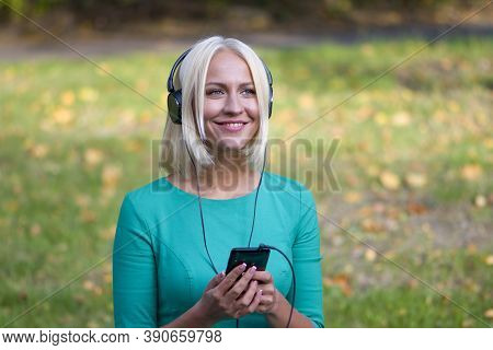 A Young Woman 25-30 Years Old In The Park Listening To Music With Headphones From Her Phone, A Happy