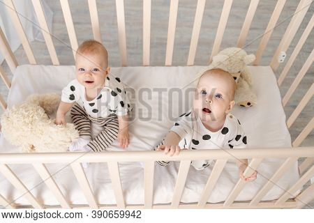 Two Baby Twins Brother And Sister 8 Months Sit In Their Pajamas In The Crib And Look At The Camera,
