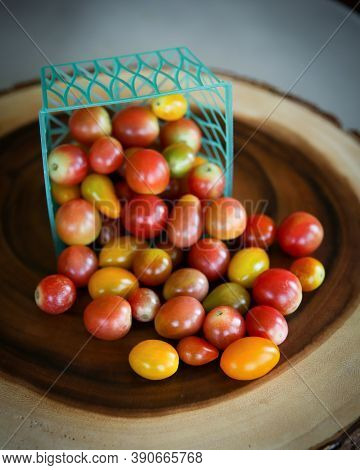 Heirloom Cherry Tomatoes Spilling Out Of A Basket On A Wood Platter.