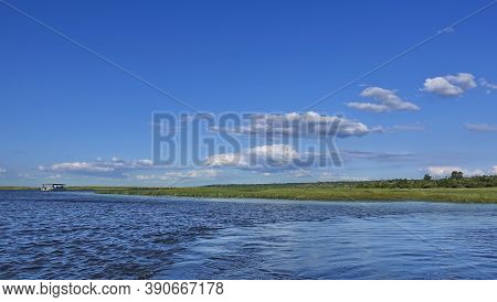 Peaceful Summer Landscape. The Blue River Flows Between Green Banks. There Are Clouds In The Azure S