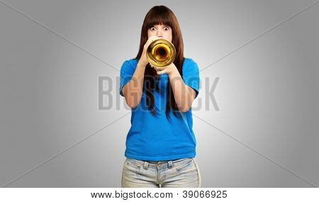 portrait of a teenager playing trumpet on gray background