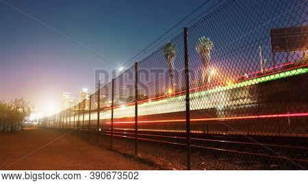 Long exposure shot of train moving towards downtown Los Angeles at night. Copyspace.