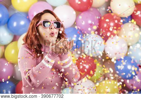 Redhair Young Woman Parties Alone, Blowing Confetti On Multicolored Balloons Background. Celebrating
