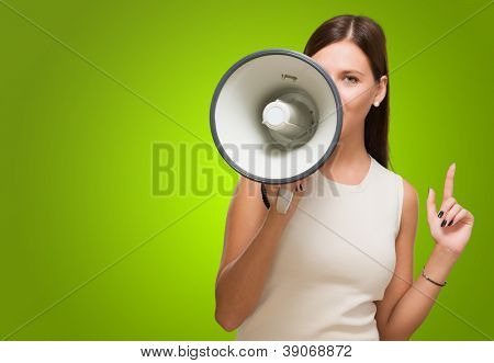 Young Woman Holding Megaphone against a green background