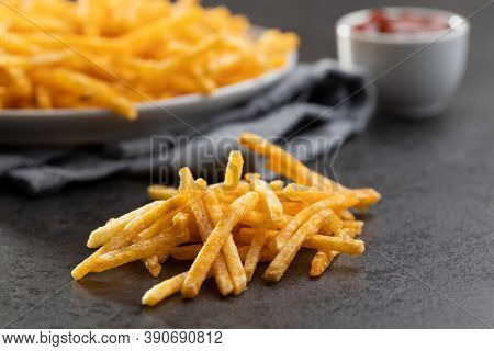 French fries. Fried mini potato sticks on black table.