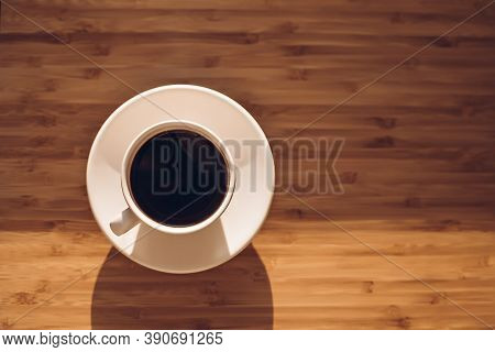 Cup Of Black Coffee On Bamboo Desk.