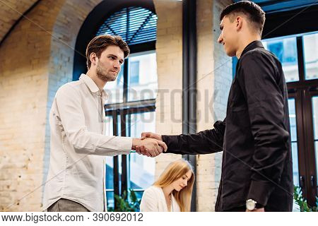Businessmen Shaking Hands In Office On Background Of Businesswoman