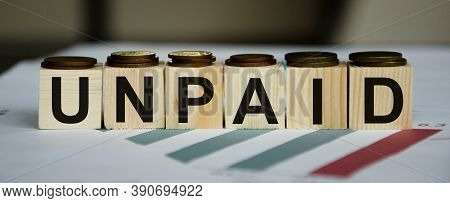 Unpaid Word Written On Wood Block. Unpaid Text On Wooden Table For Your Desing, Concept. High Qualit