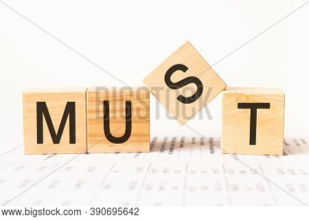 Word Must. Wooden Small Cubes With Letters Isolated On White Background With Copy Space Available.bu