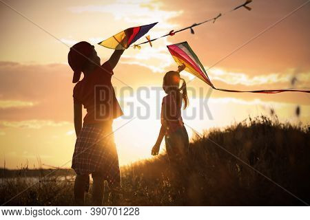 Little Children Playing With Kites Outdoors At Sunset. Spending Time In Nature