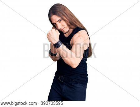 Young adult man with long hair wearing goth style with black clothes ready to fight with fist defense gesture, angry and upset face, afraid of problem