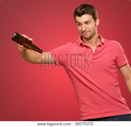 Portrait Of Young Man Holding Empty Bottle On Red Background