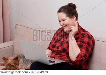 Woman Plus Size Model Communicates Online Via Video Link, Next To A Pet Dog.