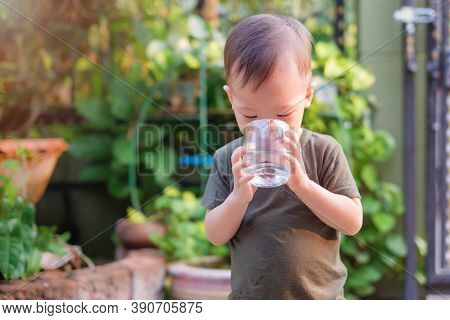 Cute Thirsty Little Asian 18 Months / 1 Year Old Toddler Boy Child Holding And Drinking Glass Of Wat