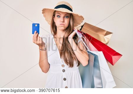 Young blonde girl holding shopping bags and credit card puffing cheeks with funny face. mouth inflated with air, catching air.