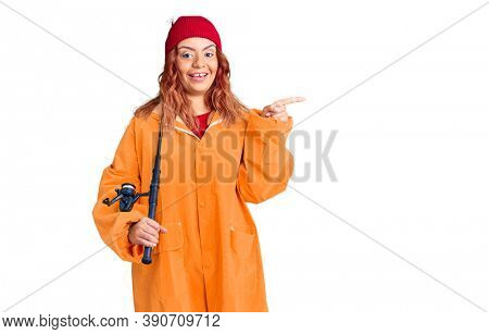 Young latin woman wearing fisher raicoat holding rod smiling happy pointing with hand and finger to the side
