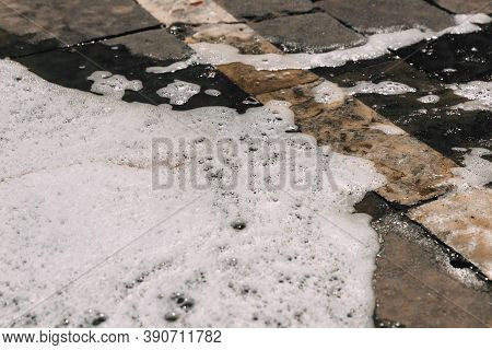 Foam Streams On The Asphalt From Car Wash, Wet Concrete Texture. Backdrop Background. Intricate Natu