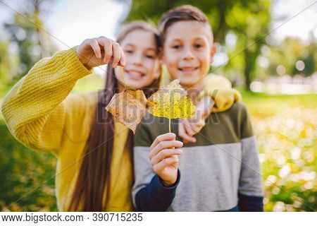 Friendship Between Siblings. Siblings Together Outside With Bright Colored Background. Kids Autumn P
