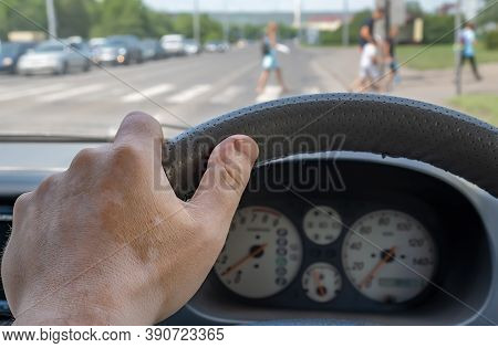 The Driver Hand On The Steering Wheel Of The Car, Which Is Standing, Waiting For People To Pass Thro