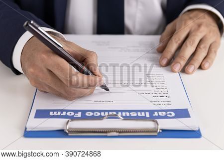 Insurance Agent Hand Writing Car Insurance Claim Form Or Insurance Document On Office Table