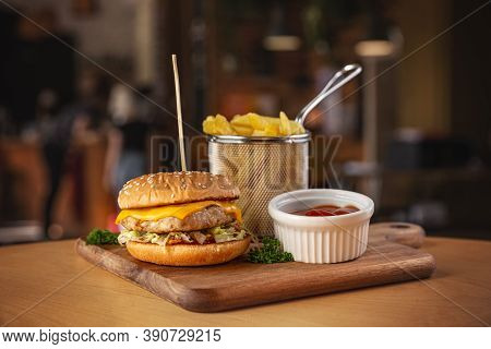 Delicious Grilled Chicken Burger Served With Fries And Hot Tomato Sauce