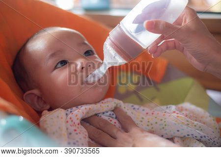 Adorable Cute Little Asian Baby Eating Tasty Food Feeding By Mother At Home