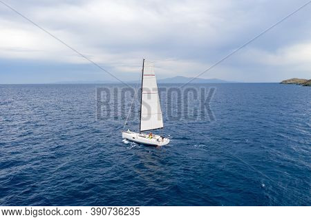 Sailing Boat With White Sails, Cloudy Sky And Rippled Sea Background