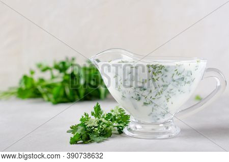 White Sauce With In A Gravy Boat On A White Background.