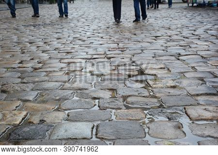 A Close-up On A Wet Durable Stone Pebbled Walkway, Cobblestone Pedestrian Shared Street Of An Old Ci