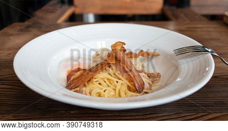 Homemade Spaghetti Carbonara With Bacon And Egg On White Plate On Wooden Table