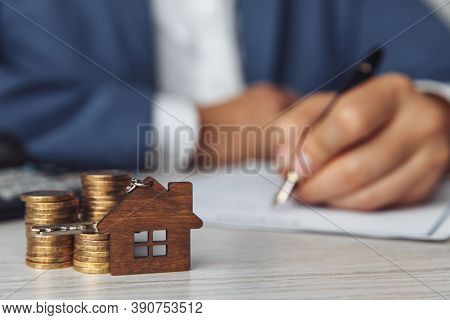 Sale Agent Signing Mortgage Loan Agreement Contract. Wooden House Shaped Keyring And Stack Of Coins
