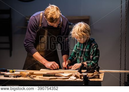 A Young Father And His Little Son Make A Toy Out Of Wood In A Carpenters Workshop