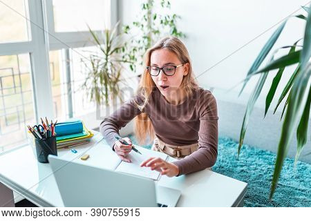 Surprised Beautiful Young School Girl Left-handed Working At Home In Her Room With A Laptop And Clas