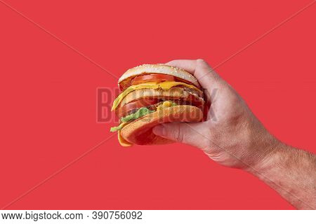 A Big, Juicy Mouthwatering Burger With Vegetables And Meatballs In His Hand.
