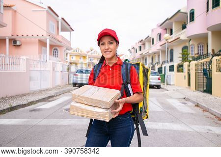 Portrait Of Pretty Postwoman Holding Parcels And Carrying Thermal Backpack. Latin Female Courier Wea