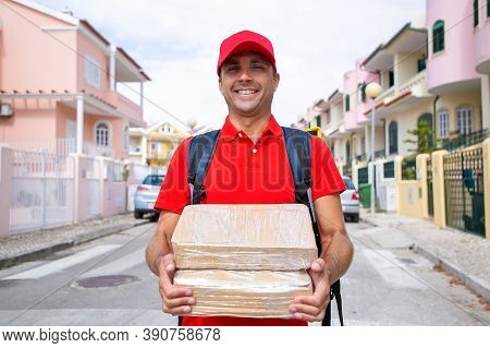 Portrait Of Cheerful Postman Holding Parcels And Carrying Thermal Backpack. Caucasian Courier Wearin