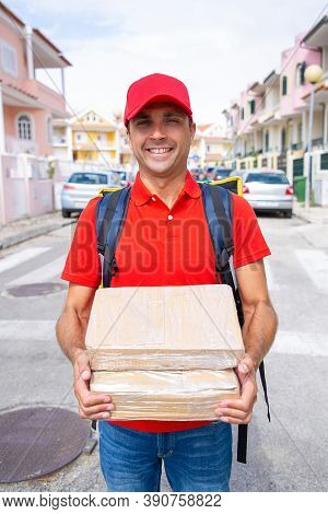 Portrait Of Happy Deliveryman Holding Carton Boxes And Carrying Thermal Backpack. Middle-aged Caucas