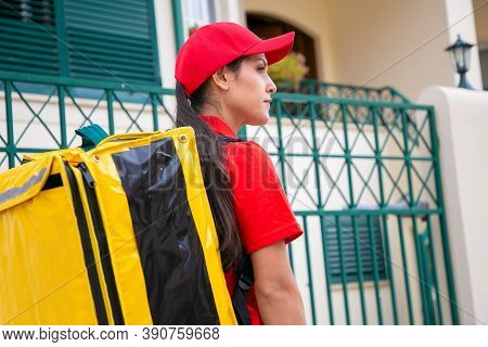 Confident Latin Courier Delivering Order And Looking Away. Professional Young Beautiful Deliverywoma