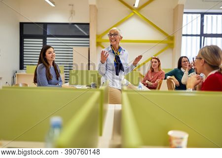 A female professor in the university classroom enjoying teaching the students. Smart young people study at the college. Education, college, university, learning and multiethnic people concept