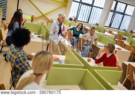 A relaxed female professor discussing a lesson with students in the university classroom. young people study at the college. Education, college, university, learning and multiethnic people concept