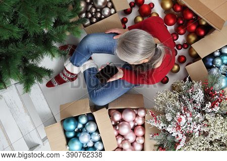 Woman With Mobile Phone Prepare Christmas Tree With Cardboard Boxes Full Of Christmas Balls And Deco