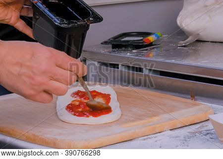 Professional Chef, Baker Hands Holding Spoon And Preparing Dough With Tomato Paste For Cooking Pizza