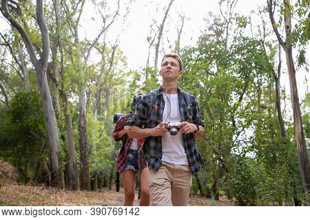Handsome Tourist Holding Camera And Looking On Scenery. Woman Hiking Behind. Two Travelers Walking O